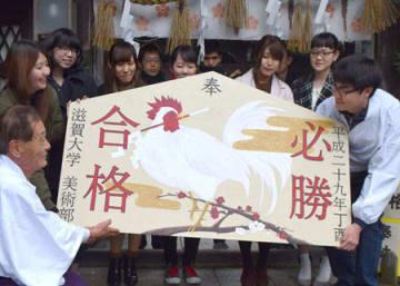 来年のえと「酉」を描いた合格祈願の絵馬を囲む滋賀大美術部のメンバーら(滋賀県彦根市馬場1丁目・北野神社)