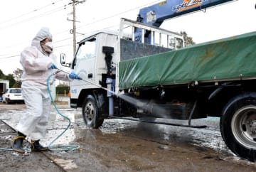 鶏肉などの移動、搬出が制限されている川南町の消毒ポイント。制限解除に向け、懸命な消毒作業が続いている=23日午後、川南町川南