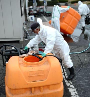 搬出制限区域の解除を受けて、消毒ポイントの撤去作業を行う関係者=5日午後、高鍋町持田