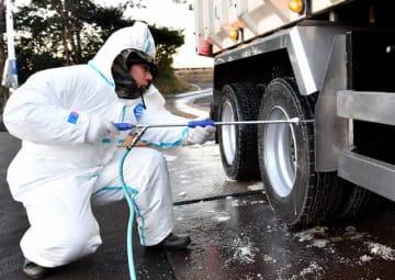 氷点下に冷え込み、凍結防止の融雪剤がまかれた道路で畜産関係車両の消毒に当たる作業員=25日午前7時22分、木城町高城