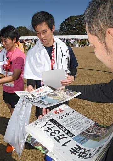 熊日の号外を受け取るフルマラソンのランナーたち=19日午後、熊本市の二の丸広場(池田祐介)