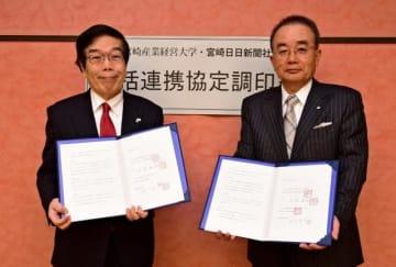 包括的連携に関する協定を結んだ大村昌弘学長(左)と町川安久社長=22日午後、宮崎市の宮日会館