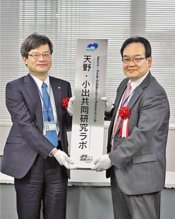 共同研究ラボのネームプレートを掲げる天野氏㊧と小出康夫氏