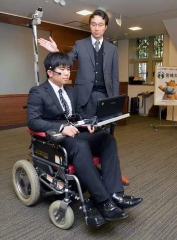 表情筋などを使い電動車いすを操作するシステムを説明する田村教授(右)=13日午後、東京・文部科学省