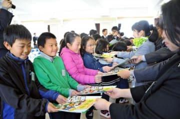 小学生向けキャリア教育の冊子を受け取る子どもたち=17日午前、宮崎市・生目台西小
