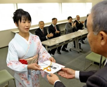 第21回県美術海外留学賞の授賞式で、町川社長から記念の盾と目録を受け取る木村さん=22日午前、宮崎市・宮日会館