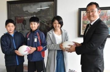 高鍋東小にラグビーボールを届けた檜室監督(右)。児童を代表してボールを受け取った(左から)吉田君、佐藤君、伊藤さん