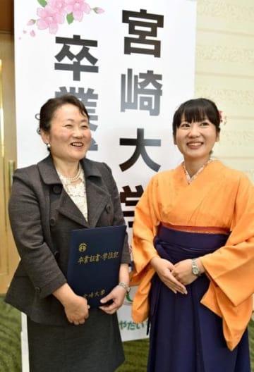 宮崎大の卒業式で笑顔を見せる秦博子さん(左)と娘の長島陽子さん(右)=24日午前、宮崎市・シーガイアコンベンションセンター
