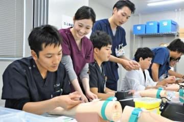 先輩医師の指導を受けながら、採血や縫合など基礎的な処置を実践する新研修医=4日午後、宮崎市・宮崎大医学部臨床技術トレーニングセンター
