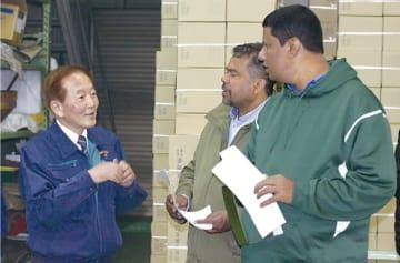 工場を案内するトーカンの筒井社長(左)