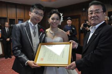 田村副市長(右)から婚姻受理証明書を受け取る新郎新婦=11日午後、宮崎市役所
