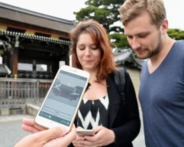 京都御所の建礼門前で、音声解説するスマホアプリを見る外国人観光客(16日午後4時50分、京都市上京区・京都御苑)