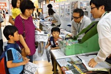 土石流災害の怖さを伝える模型の展示に見入る来場者=27日午後、宮崎市・イオンモール宮崎