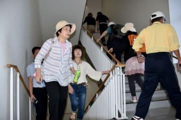避難訓練で屋上を目指して階段を上る住民ら=28日午前、宮崎市阿波岐原町の県総合自動車運転免許センター