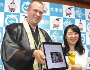 フェイスブックに投稿した石山寺の写真を見せる、大津市のPR大使に就任したジェシー・ラフィーバーさん(左)と越直美市長=大津市役所