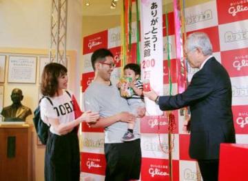 記念式典で江崎勝久社長(右)からグリコ製品の詰め合わせを贈られる200万人目の来館者となった河井さん家族=15日、神戸市西区