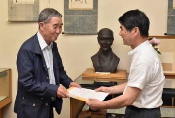 秋田雨雀の胸像前で、所蔵品の寄贈書を取り交わす遺族の秋田さん(左)と伊藤館長