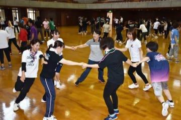 さまざまな運動を体験し、子どもたちへの指導方法を学ぶ幼稚園の教諭ら=19日午前、宮崎市