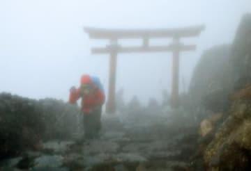 山開きを迎えた富士山で、暴風雨のなか山頂を目指す登山客=1日午前4時40分