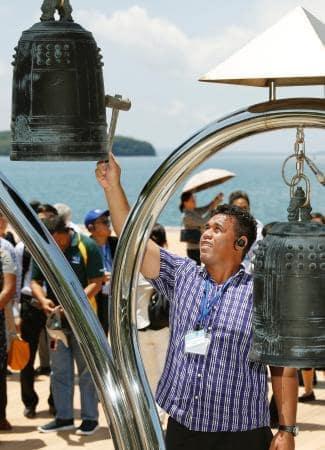 水俣病犠牲者の慰霊碑を訪れ、鐘を鳴らす「水銀に関する水俣条約」発効記念行事の参加者=1日、熊本県水俣市