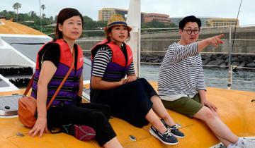 漢拏日報の担当者(右)の説明を聞きながらクルージングを楽しむ島さん(左)と木滝さん=2日、韓国・済州島
