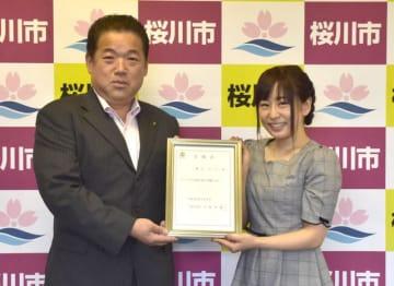 大塚秀喜市長(左)から委嘱状を受け取った櫻川めぐさん=桜川市羽田