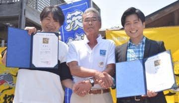 小田部卓社長(中央)から委嘱状を渡されたマシコタツロウさん(左)と磯山純さん=ひたちなか市阿字ケ浦町