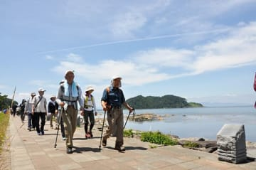 快晴の夏泊半島を歩く参加者たち