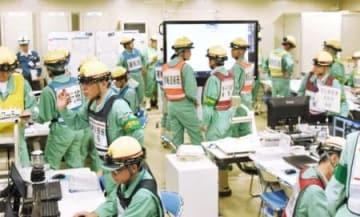 伊方原発の重大事故を想定した総合訓練で、緊急時対策所で対応する四国電力の社員ら=13日午前、愛媛県伊方町
