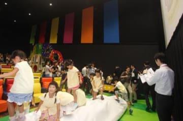 スクリーン前の遊具で飛び跳ねる保育園児たち。奥に見えるのが滑り台=イオンシネマ常滑