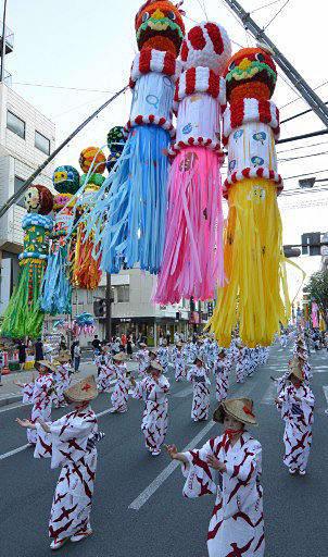 鮮やかな七夕飾りの下、各団体の隊列がゆったりとしたリズムの舞を披露した