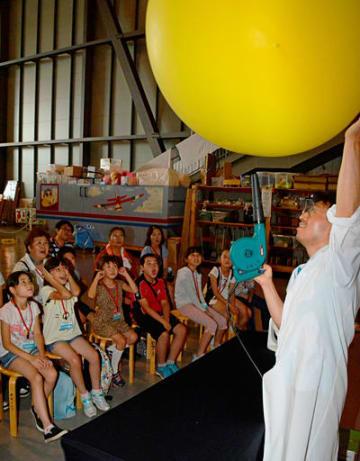 ブロアーで大きな風船を吹き上げる実験に驚く子供ら=三沢航空科学館