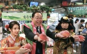 23日、台北市内のスーパーでモモをPRする山梨県の後藤斎知事(中央)(共同)