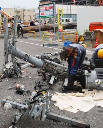 落下して市道をふさいだ鋼管(奥)と倒れた電柱=近江八幡市鷹飼町