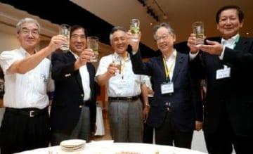 「いいちこナチュラルフレーバー グリーンティー」の水割りで乾杯する谷口太一郎市長(左から2人目)や三和酒類の和田久継社長(右端)ら=嬉野市の和多屋別荘「ザ・コットンクラブ」