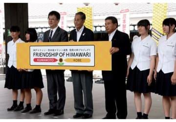 パートナーシップ協定を交わした大西市長と西川公明神戸マラソン実行委会長(写真中央)ら=熊本市中央区