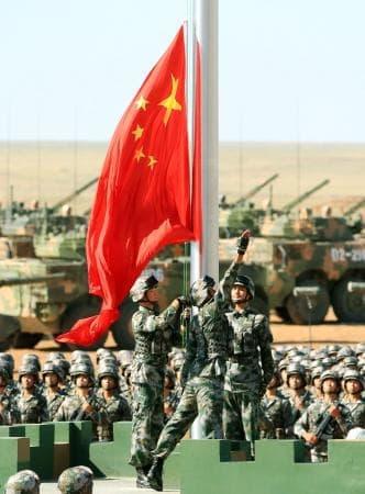 中国人民解放軍の創設90周年を記念した閲兵式で、国旗掲揚する兵士たち=30日、中国内モンゴル自治区(新華社=共同)
