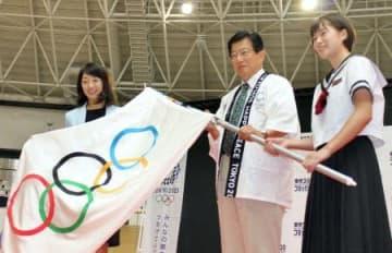 岩崎恭子さん(左)から五輪旗を手渡された静岡県の川勝平太知事=30日、静岡県伊豆市の「伊豆ベロドローム」