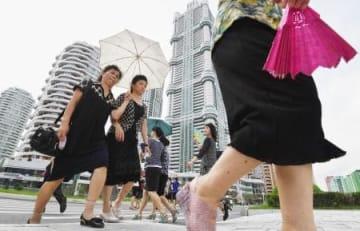 7月、平壌の高層住宅団地「黎明通り」を日傘を差し行き交う女性たち(共同)