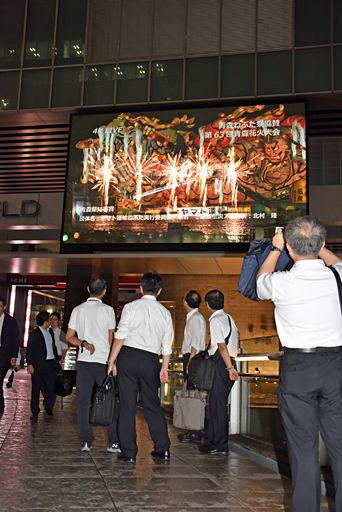 大型ビジョンに映し出されたねぶた海上運行に見入ったり写真に収める通行人たち=7日夜、東京・秋葉原