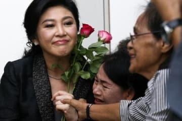 タイの首都バンコクの最高裁に着き、支持者にあいさつするインラック前首相(左)=1日(ロイター=共同)