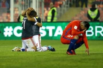 ゴールを喜ぶパラグアイの選手たち(左)と、すぐ横でしゃがみ込むチリのメデル=31日、サンティアゴ(ロイター=共同)