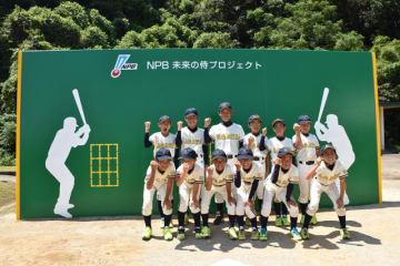 「ベース・ウォール」の前で笑顔を見せる吾田少年野球クラブのメンバーや監督