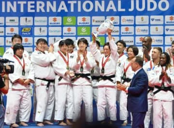 柔道世界選手権の男女混合団体戦決勝で、ブラジルを下し優勝、表彰台で喜ぶ日本選手=3日、ブダペスト(共同)