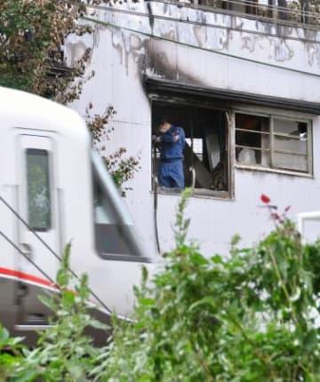 小田急小田原線の電車の屋根に火が燃え移った火災で、出火元の「オザキボクシングジム」が入る建物を実況見分する警視庁の捜査員=11日午後、東京都渋谷区