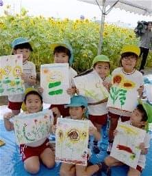 満開のヒマワリを描いたスケッチを手にする園児。はじける笑顔のような作品が出来上がった=14日、熊本市西区