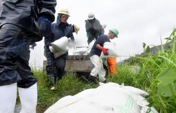 台風18号の接近に備え、加江田川の河川敷に土のうを積む人たち=16日午後、宮崎市加江田