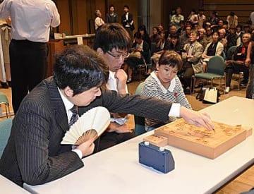 県将棋まつりの席上対局で3人対3人の連将棋を指す、行方八段(左)と県内アマ強豪ら=17日、青森市のアウガ
