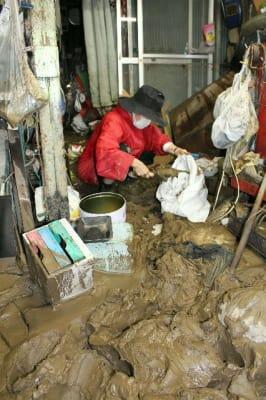 自宅や作業場にたまった泥を土のう袋に詰める、津久見市宮本町の染矢ミユキさん=18日午前10時52分