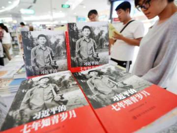 共産党大会を前に発売され、書店に積まれた「習近平、知識青年としての7年」=15日、北京(共同)